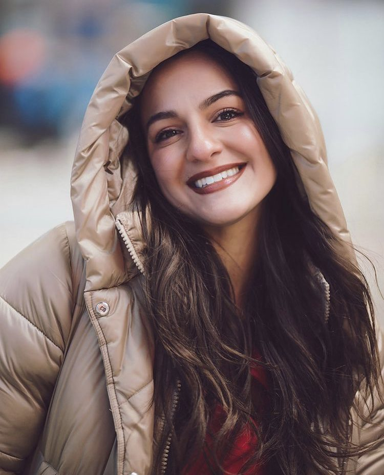 Girl smiling with brown hair wearing a tan coat with the hood up