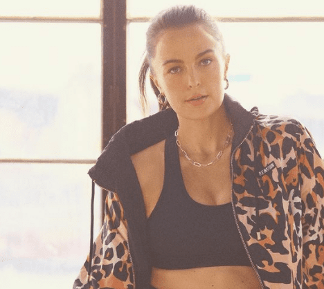 Photo of Megan Roup with a leopard jacket on a black set with shorts in front of a window
