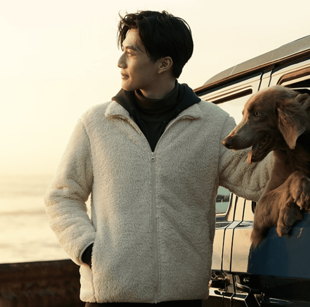 Photo of man wearing UNIQLO jacket with a golden retriever in a car